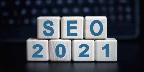 SEO 2021 concept - text in wooden cubes on a black keyboard.